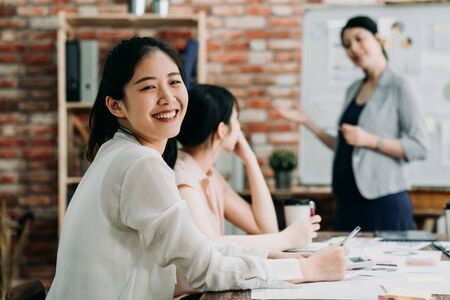 confident beautiful female worker looking at camera posing and smiling. pretty women partners sitting and having discussion during colleagues corporate meeting. Imagens