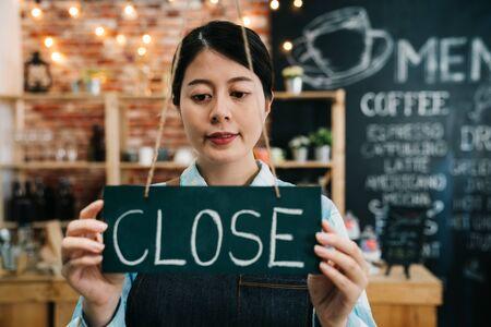 Closed sign black board in woman hands hanging on window of door in coffee shop.