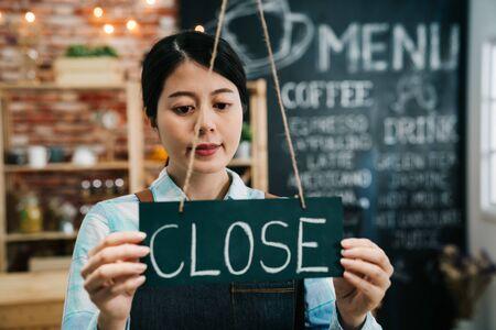 Beautiful asian woman in barista apron holding close blackboard sign inside coffee shop. Stock fotó