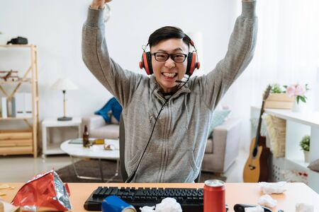 Happy young Asian chinese man playing and winning online game on computer.