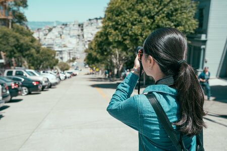 female travel photographer standing on sunny day on downtown road taking photo in san francisco.