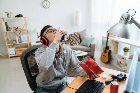 male student playing online game in messy dormitory eating pack of chips and drinking can of ice beer.