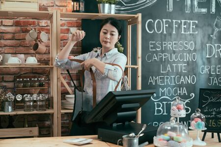 early morning female barista open cafe store and begin good day wearing on professional apron in wood counter.