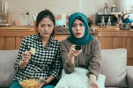 Group of female friends sit on sofa in bright dining room and watching horror movie holding breath.