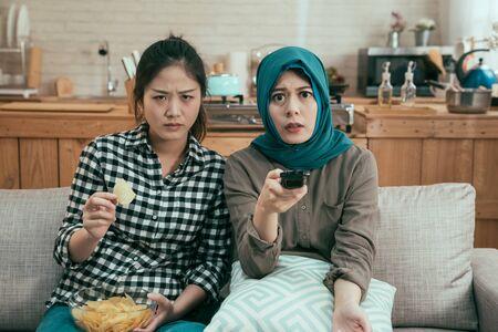 Un groupe d'amies s'assoit sur un canapé dans une salle à manger lumineuse et regarde un film d'horreur en retenant son souffle.