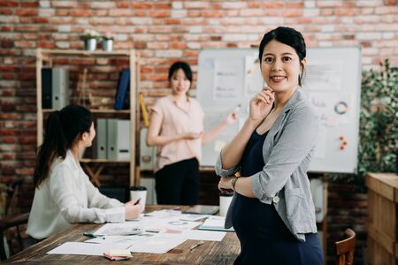 Confident young Asian pregnant businesswoman standing with folded arms smiling at camera in boardroom with female colleagues discussing in background. group of women creative team in meeting.