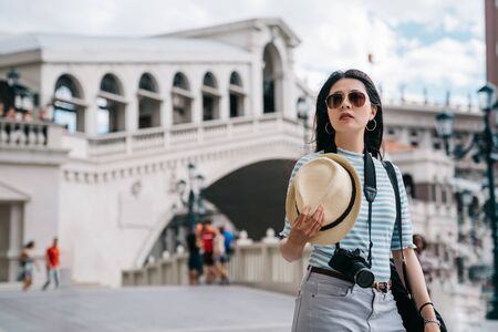 Young charming asian woman traveler taking straw hat and looking aside while walking on street outdoor on sunny day. girl tourist crossing bridge in las vegas strip. female photographer search road. Stock fotó