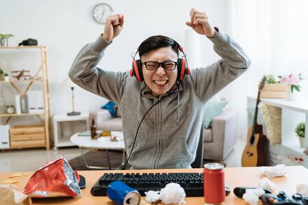Excited overjoyed lucky asian man screaming with joy looking at camera in messy bedroom on summer break time. guy in headphones celebrating win triumph rejoicing victory on computer online game. 写真素材