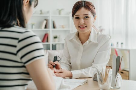Beautiful girl manicurist doing manicure for woman client in apartment. young confident lady beautician face camera and giving attractive smile while working in nail home service. nail specialist. 写真素材