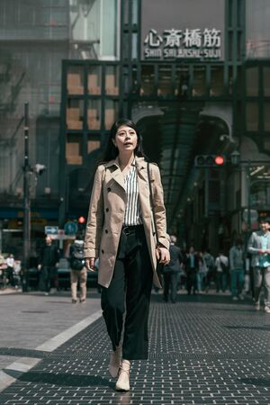 Young beautiful asian woman worker in beige coat with bag walking on autumn street in shinsaibashi area.