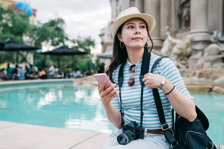 smiling girl traveler with bag and camera sit by pound looking side