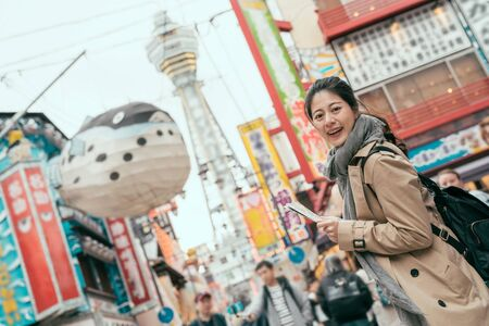 side view of young girl standing in dotonbori and shinsaibashi.