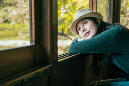 inside view with young girl traveler wearing straw hat leaning against open window in house.