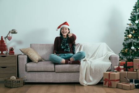smiling woman sit on couch with tv remote control on home couch by christmas tree white background. Stockfoto