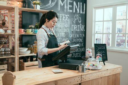 Jeune serveuse japonaise asiatique utilisant un appareil numérique pour le paiement au comptoir du café. Banque d'images