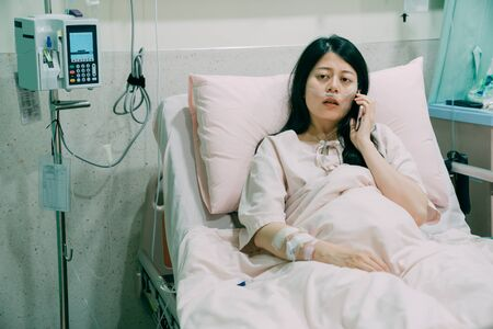 unhappy young Asian chinese female patient talking on mobile phone in bed. attractive sick woman lying on bed in hospital room. illness people connected world and mobile office concept.