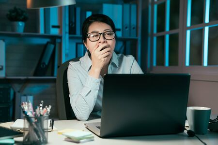 business overwork deadline and people concept. tired asian japanese woman with laptop computer working at night office and yawning. exhausted young office lady in glasses feeling sleepy cover mouth