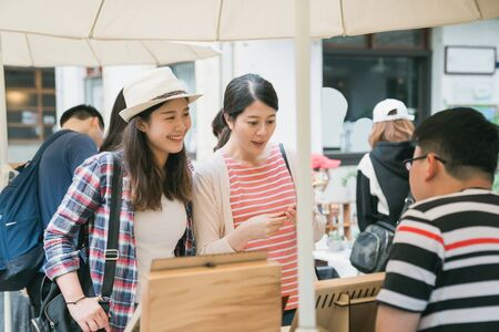 group of young female tourists at weekly creative market.  Best friends sharing free time on weekend having fun and shopping in old town tokyo japan. smiling girl guests looking at vendor seller.