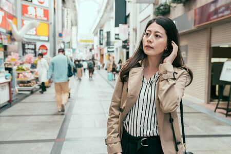 Beautiful elegant young girl with long hair wearing spring coat walking on city street in casual style. lady shopping and buying souvenir in business trip. woman looking curiously in shinsaibashi Stock Photo