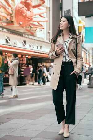 full length of japanese businesswoman using smartphone with online map app searching ways to visit famous local restaurant. Happy asian woman worker standing in dotonbori street and find lunch. Stock Photo