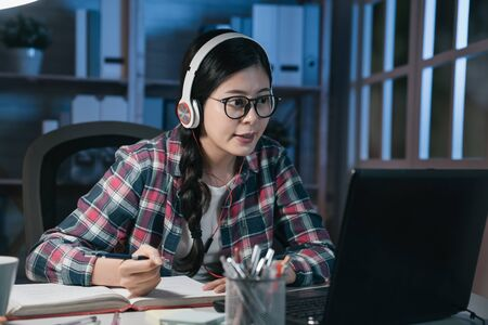 Sonriente mujer asiática japonesa estudiante e-learning comparando notas sentado en el escritorio en la noche en casa. Joven universitaria en auriculares escuchando un curso en línea en una computadora portátil y haciendo notas escribiendo