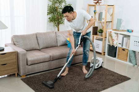 Young asian japanese man cleaning carpet with vacuum cleaner at home living room. handsome guy doing housework in bright modern apartment. male household hardworking prepare tidy up for new year.