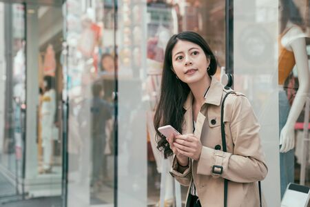 Young asian japanese woman using smartphone while standing in shopping district of city with a fashion store window in background. smiling girl searching direction on mobile phone in modern urban. Stock Photo