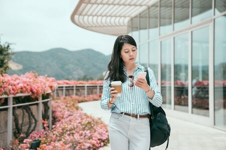 Portrait of beautiful young asian japanese business woman using mobile phone in work building outdoor. office lady going to company walking while holding cup of morning coffee by pink flower garden 스톡 콘텐츠