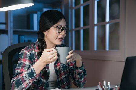 young attractive Asian Chinese woman stay up late at night using internet in laptop computer and studying for final exam. charming smiling college girl student drinking cup of tea in lifestyle 版權商用圖片
