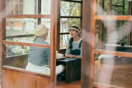 group of asian girl friends sitting by window of jinya governor room. two beautiful ladies in summer hats chatting and talking during tea ceremony in japanese style wooden house. friendship leisure.