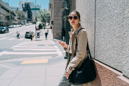 Young attractive woman in sunglasses stands outside on wall background. beautiful asian lady looking side and holding mobile phone. charming girl waiting friends on street lifestyle in summer time.