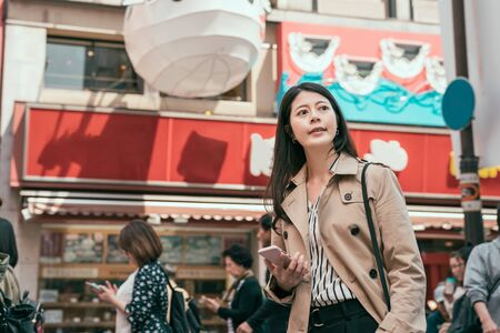 Positive young woman walking in japan city looking at side store while holding smart phone searching way. elegant lady in coat travel in osaka in spring. female with cellphone finding direction Stock Photo