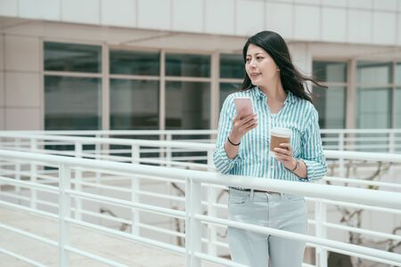 young smiling asian chinese businesswoman walking on bridge outdoor in office work center using smartphone. happy relax lady enjoy break time texting message on mobile phone and holding cup of coffee