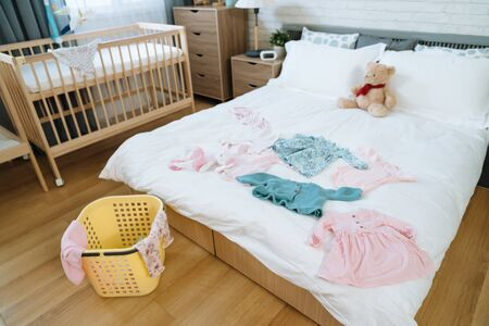view of master bedroom with some baby clothes scattered on white bedding. bright chamber of parents-to-be who are expecting their first baby girl.
