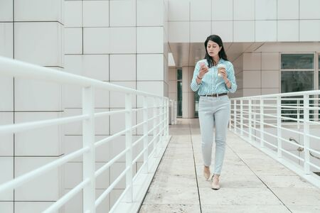 full length of elegant young office lady walking in sky corridor outdoor in skyscraper. confident female business people using cellphone and holding takeaway coffee enjoy sunshine on bridge. Foto de archivo