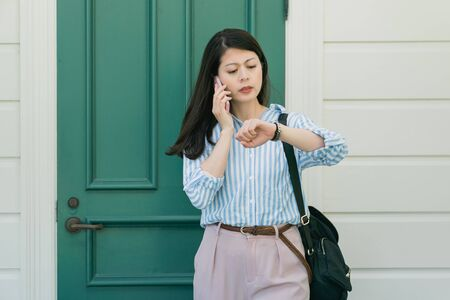 Hurry up! Portrait of responsible attractive asian woman having important call speaking by smart phone looking at luxury watch on wrist. frowning young girl talking on cellphone telling to be quick Foto de archivo
