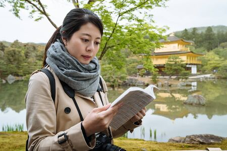korean visitor to Kintakuji is reading guidebook for information attentively on the shore of pond. woman tourist is looking at reference book to learn the history of the cultural heritage at lakeside