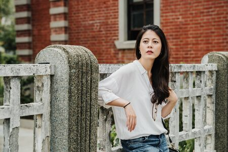 beautiful asian chinese girl tourist in white shirt and jeans leaning on railing with red brick wall against in background. elegant charming female traveler enjoy sunshine outside old town monument