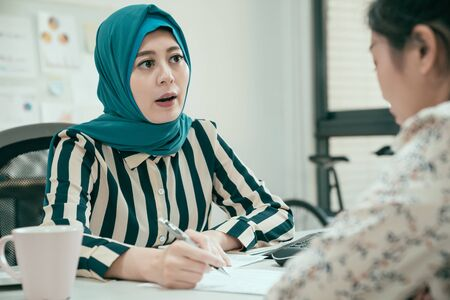 group of young asian muslim and chinese women having business meeting and signing contract in office. recruitment and agreement concept. elegant islam lady worker talking and explaining about project Фото со стока