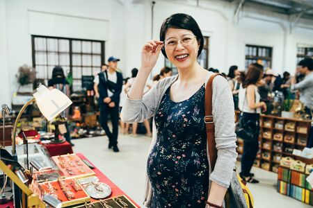 joyful young asian korean motherhood woman choosing glasses in optician store vendor in summer holidays market indoors. happy pregnant female face camera smiling while trying on new eyeglasses.