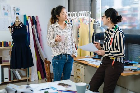 startup education fashion and studio concept. two asian smiling female designers having coffee break in office. group of creative team relax in workshop while discussing on sketch and drinking tea.