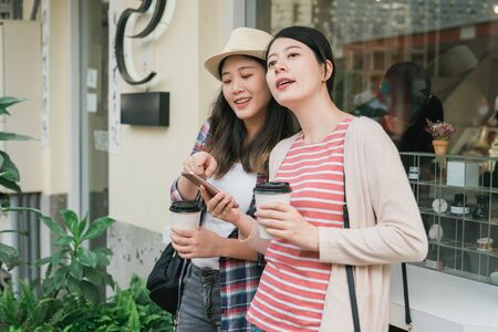 Two attractive young asian chinese woman holding paper coffee cups and looking at mobile phone together while standing outdoors by little shop. girl friends tourist searching direction on cellphone.