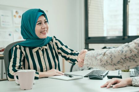 Business people shaking hands finishing up meeting in office. smiling young beautiful muslim lady worker in blue hijab handshaking with female customer in workplace sit at desk. cooperation concept Фото со стока