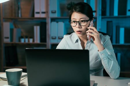 confident businesswoman in glasses overtime work and speak on smart phone. beautiful office lady hardworking on laptop computer in dark night at company and talking on cellphone with coworker.