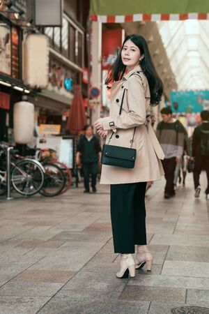 full length asian girl walking in busy city street with long hair flying on wind. Woman turning around looking at camera outdoors wearing fashionable high heels shoes. osaka city japan lifestyle
