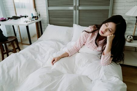 lack of energy asian woman feel miserable and doesn't want to get out bed. japanese female sitting in bed is propping her head, lost in daze.