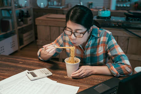 casual asian japanese woman blowing on hot instant noodles while eating with chopsticks sitting at wooden dining table in kitchen. hungry lady in midnight enjoy bedtime snack during over work time. Standard-Bild