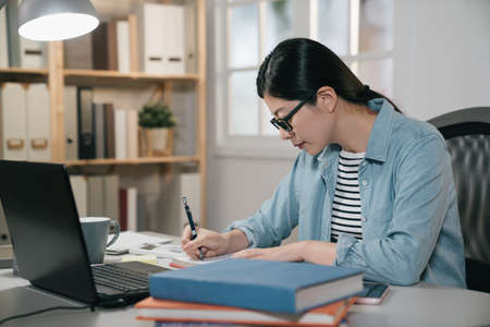 Female student taking notes from book at home. Young asian japanese woman sitting at table doing assignments for final exam project at school. side view of smart elegant college girl doing homework.