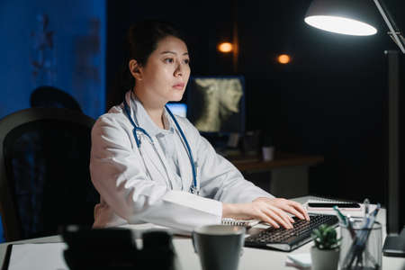 asian chinese female doctor working on desk with computer in hospital office. Concept of medical healthcare patient data record analysis. young girl clinic staff typing and replying problem in night 免版税图像