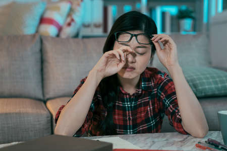 korean girl getting tired eyes from studying throughout night without resting. asian female student with asthenopia is rubbing her eye and struggling to focus her vision. health and eye care concept